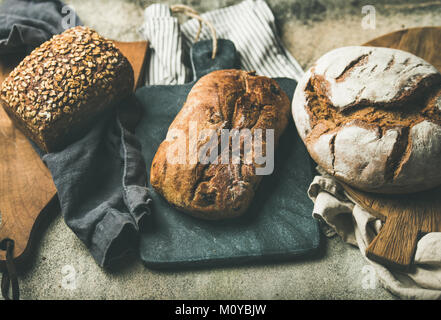 Various bread selection. Rye, wheat and multigrain rustic bread loaves on kitchen towels and wooden boards over - Stock Photo