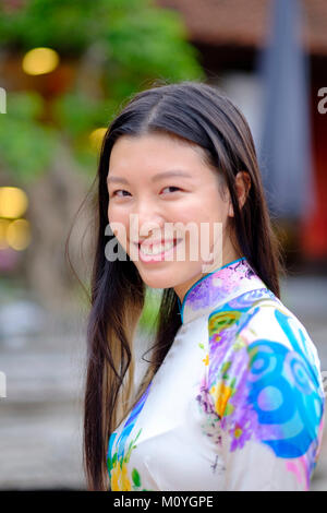 Vietnamese woman smiling and wearing a traditional Ao Dai dress - Stock Photo