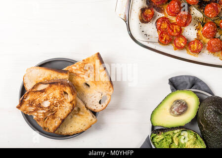 Pieces of toasted white sourdough bread with fresh ripe avocado and slow-roasted cherry tomatoes nearby - Stock Photo