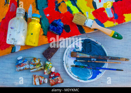Painting supplies on table with canvas - Stock Photo