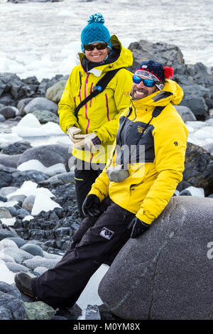 Two professional mountain guides chat on rocky beach; Half Moon Island; Antarctica - Stock Photo