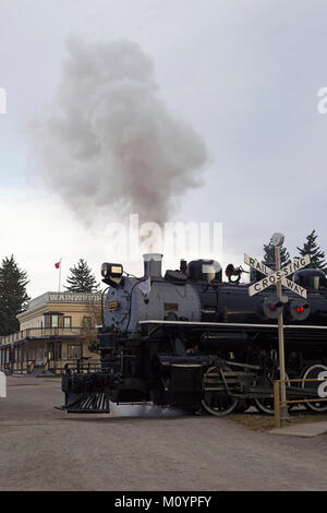 Historic steam train at railway crossing Heritage Park Historical Village - Stock Photo