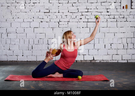 Yoga vegetarianism. Yoga girl is holding smoothies and apple. Concept of healthy life. Sporty pretty woman loves - Stock Photo