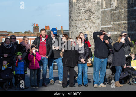 Windsor, UK. 25th January, 2018. Tourists shield their eyes from the sun as they watch the Changing of the Guard - Stock Photo