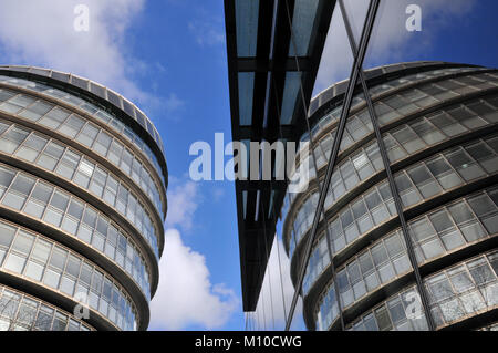 London, UK. 25th Jan, 2018. City hall on the South bank of the river Thames reflected in a contemporary glazed business - Stock Photo