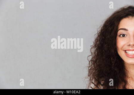 Close up half-face portrait of attractive curly woman with ring in nose posing on camera smiling with perfect white - Stock Photo