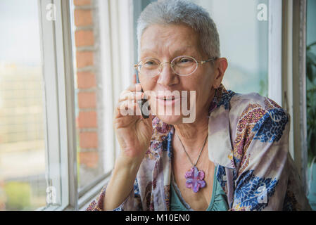 Senior woman having a friendly talk on her cell phone - Stock Photo