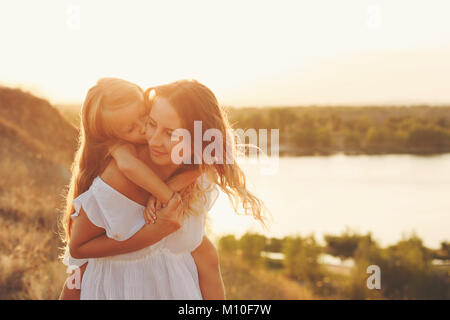 Mother Piggyback the daughter. Little girl is happy and kisses mother on cheek. Family fun in the countryside. In - Stock Photo