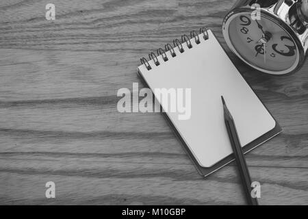 Business Creative and Idea Concept : Used pencil put on notebook with silver alarm clock put on wooden table in - Stock Photo