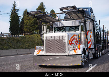 Classic big rig semi truck with square grille and two story compact car hauler semi trailer running on the road - Stock Photo