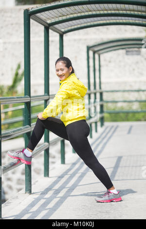 A portrait of a young asian woman stretching outdoor in yellow neon jacket - Stock Photo