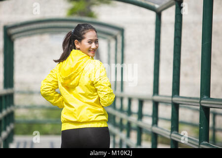 A portrait of a young asian woman exercising outdoor in yellow neon jacket - Stock Photo