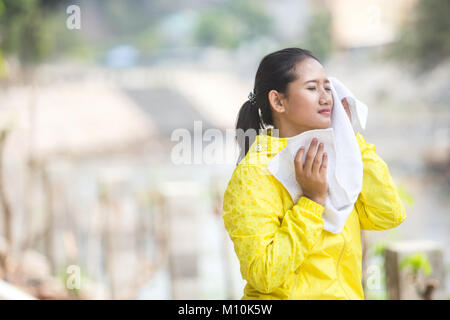 portrait of a young asian woman exercising outdoor in yellow jacket, wiping her sweat with a towel - Stock Photo