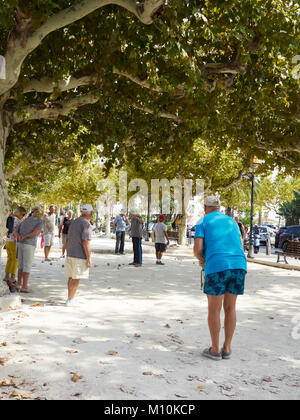 People playing a game of boules in Le Lavandou, France - Stock Photo