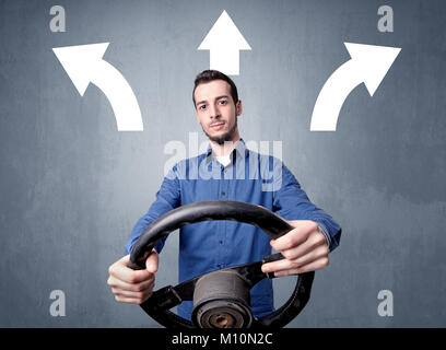 Young man holding black steering wheel with three arrows above his head pointing in different directions - Stock Photo