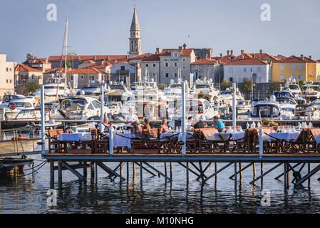 Restaurant on a pier with view on Old Town in Budva city on the Adriatic Sea coast in Montenegro - Stock Photo