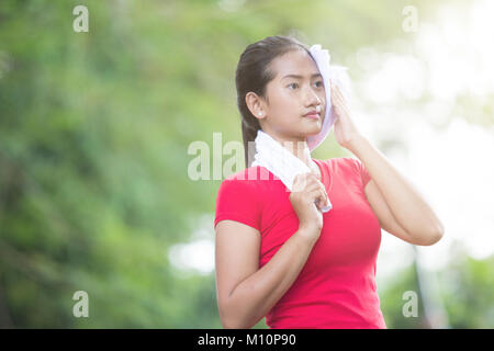 A portrait of an Asian woman wiping her sweat after exercise - Stock Photo