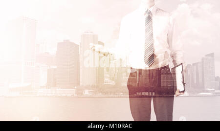 Businessman standing at cityscape background with warm light - Stock Photo