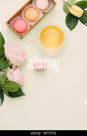 Colorful macaroons and rose flowers with tea on light green. Sweet macarons in gift box. Top view - Stock Photo