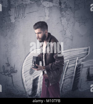 A handsome hipster guy with beard and sunglasses standing in front of an urban wall with graffiti concept - Stock Photo