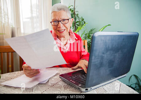 Senior woman outraged with bills from electricity company - Stock Photo