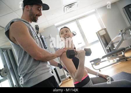 Fitness girl working out with personal trainer in gym - Stock Photo
