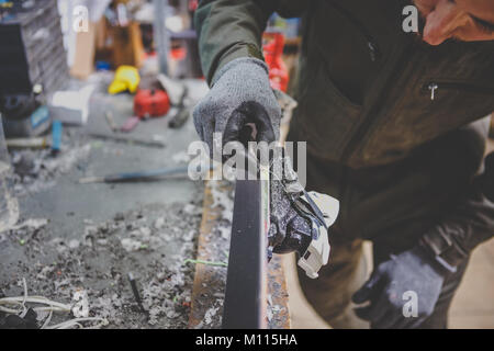 A man repairman in workshop ski service repairing the sliding surface of the ski at Ski vise. In hands of instrument - Stock Photo