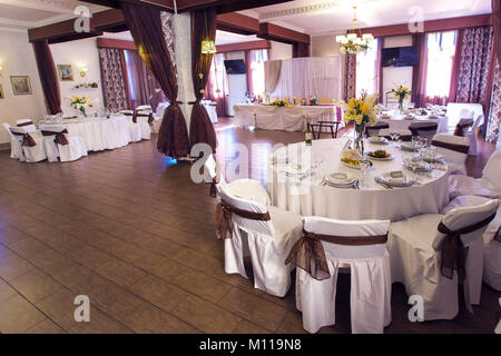 wedding hall which houses the banquet tables. On tables laid out plates, forks, knives. The table is decorated with - Stock Photo