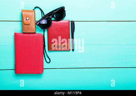 a set of traveler. sunglasses, a pen, an e-book, passport, portable camera, top view, on a wooden turquoise background - Stock Photo