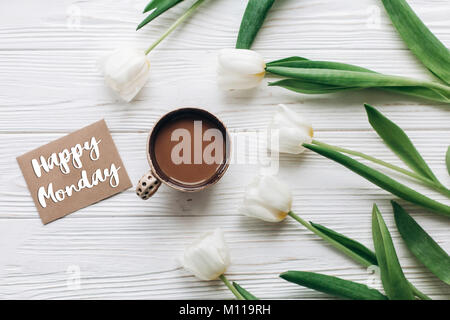 happy monday text sign on greeting card with tulips and morning coffee on white wooden rustic background with space - Stock Photo