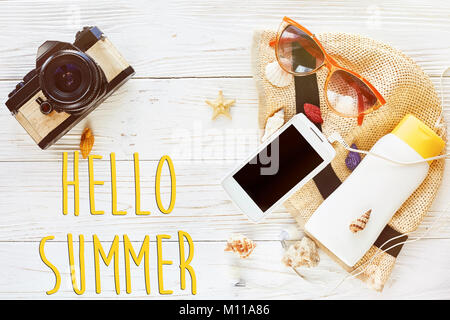 hello summer text, travel vacation flat lay concept. photo camera and hat sunscreen phone with empty screen and sunglasses on white wooden background,