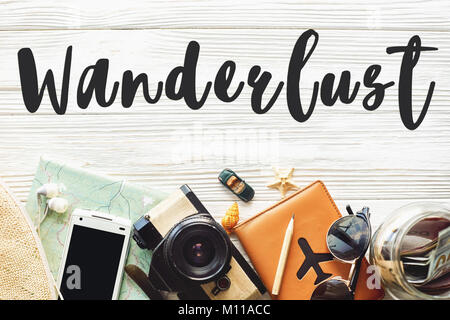 wanderlust text sign. travel concept on white background flat lay. camera sunglasses passport money map phone hat - Stock Photo
