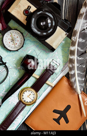 wanderlust and travel concept, hipster flat lay. map passport compass and glasses photo camera pipe on black wooden - Stock Photo