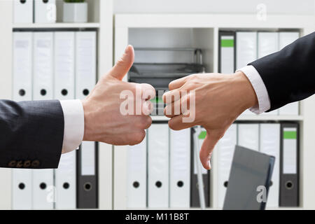 Close-up Of Business Man's Hand Showing Thumbs Up And Down In The Office - Stock Photo