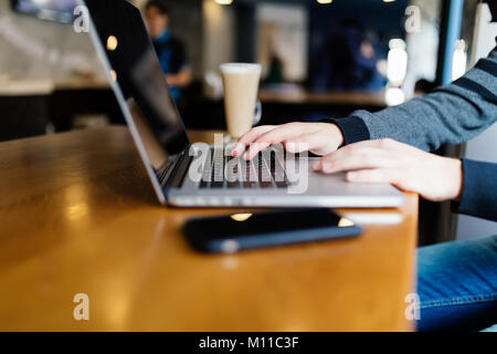 Casual business man working on laptop computer with book, notebook, mobile smartphone and cup of coffee on table - Stock Photo