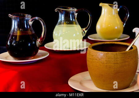Glass decanters with pomegranate sauce, lemon sauce and a mustard. Clay yellow pot - Stock Photo
