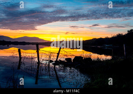 Sunset over Lake Shanaghan, Ardara, County Donegal, Ireland. silhouette of farm fencing - Stock Photo