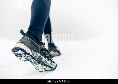 Hiking or walking shoes on snow, winter mountains.  People power walking on snow, white winter day. Female hiker - Stock Photo