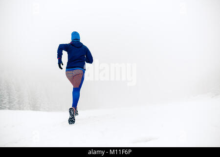 Woman trail running on snow in winter mountains and forest. Sport, fitness inspiration and motivation. Young happy - Stock Photo