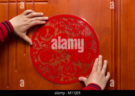 man sticking a Chinese New Year of the Dog 2018 to a door the Chinese means fortune - Stock Photo