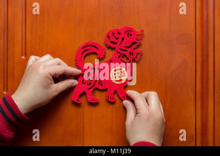 man sticking a Chinese New Year of the Dog 2018 to a door the Chinese means prosperous - Stock Photo