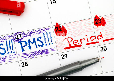 Reminder PMS and Period in calendar with red pen. Close-up. - Stock Photo