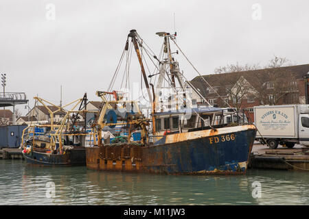 Fishing boat or trawler tied up in the docks in old Portsmouth spice island. grey day with no people around. - Stock Photo