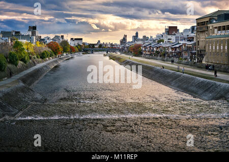 Kamo River, Kamo-gawa, with Shijoo bridge in the background in a beautiful dramatic sunset autumn city landscape - Stock Photo