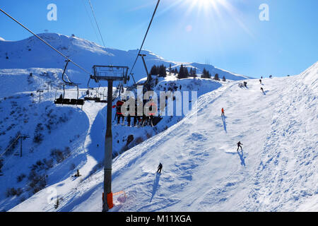 View of Skiers from the chair lift on a Sunny ski piste Samoens France - Stock Photo