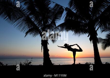 Indonesia, Island Bali, near Tejakula village, Gaia Oasis Resort. Woman performing yoga exercise at sunrise. - Stock Photo