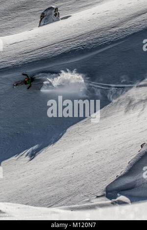 A skier skis off piste in the French alpine ski resort of Courchevel. - Stock Photo