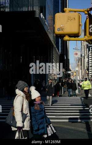 Mother and daughter waiting for traffic light on Fifth Avenue and 42nd Street.Manhattan.New York City.USA - Stock Photo