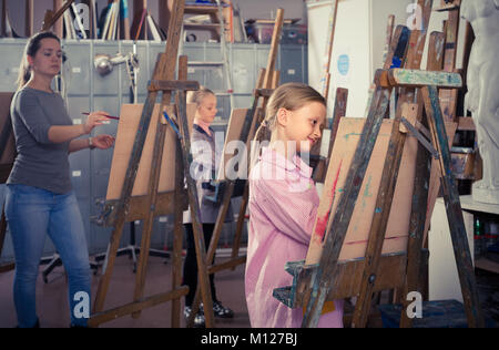 happy germany schoolgirls diligently training their painting skills during class at art studio - Stock Photo