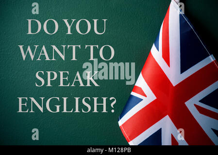 a flag of the United Kingdom and the question do you want to speak English? against a dark green background - Stock Photo